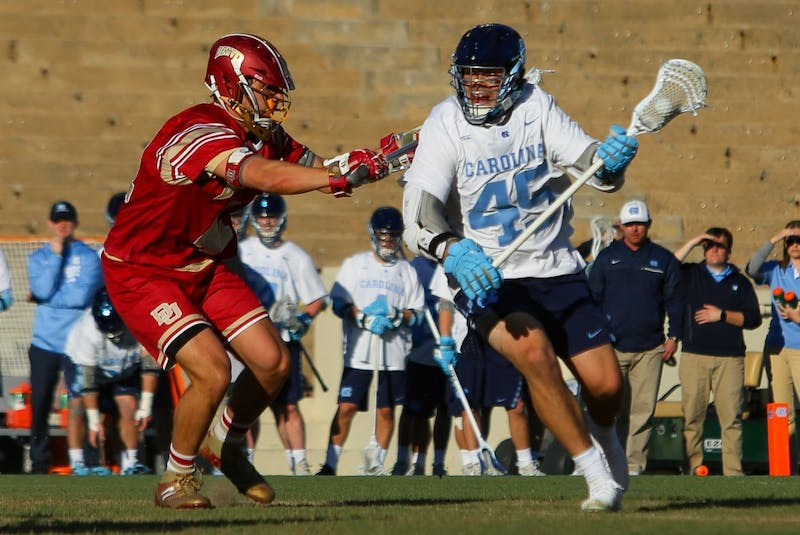 North Carolina senior attackman Chris Cloutier (45) is checked by a Denver defenseman on March 5 at Kenan Stadium.