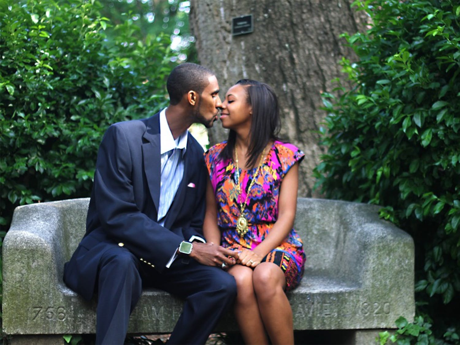 Warche Downing, a 2013 graduate of the Univeristy of North Carolina at Chapel Hill, travelled back to his alma mater in order to propose to his girlfriend, Briana Roach. They share a kiss on the Davie Poplar bench fulfilling the superstition of marriage.