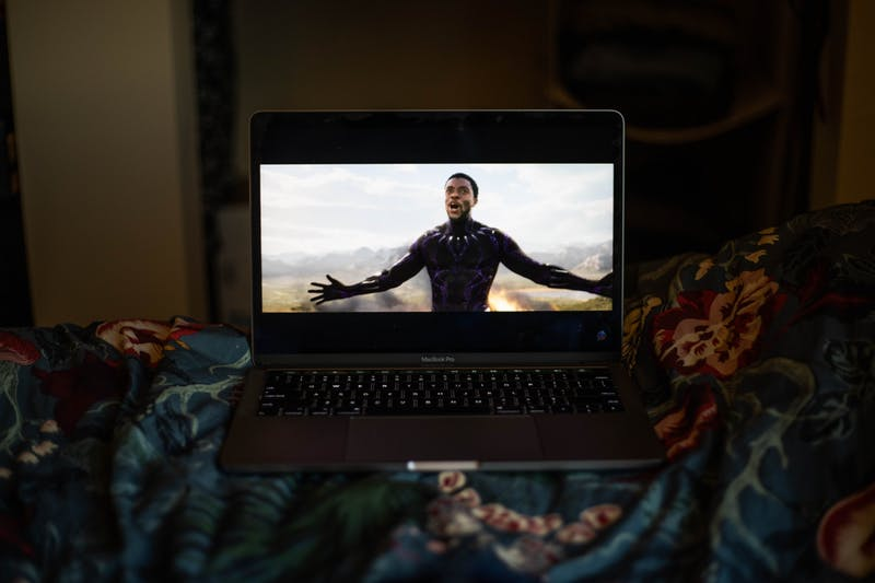DTH Photo Illustration. A student watches Black Panther in memory of the late Chadwick Boseman. Boseman died on Friday, Aug. 28, 2020 after a four-year battle with colon cancer.
