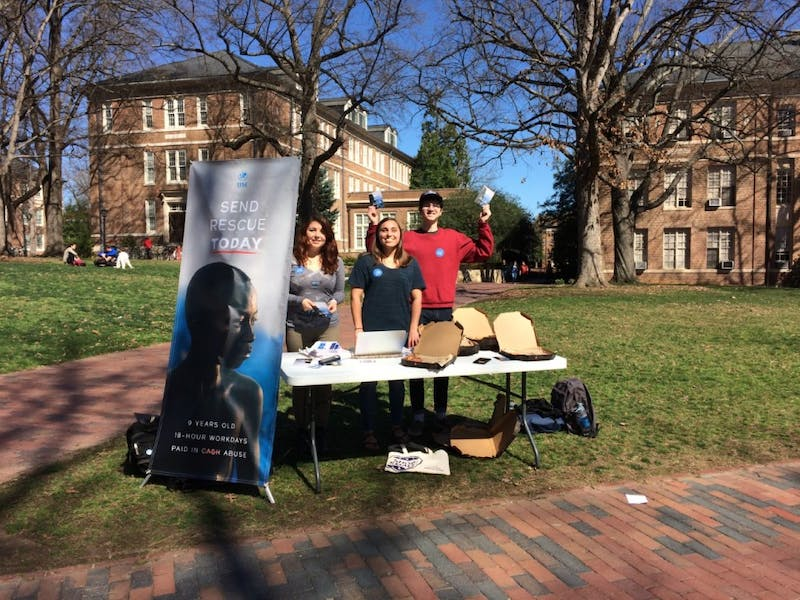 Junior Michelle Hugo, senior Mandy Spalding and sophomore Parker Marshall  staff a table for UNC's chapter of the International Justice Mission.
