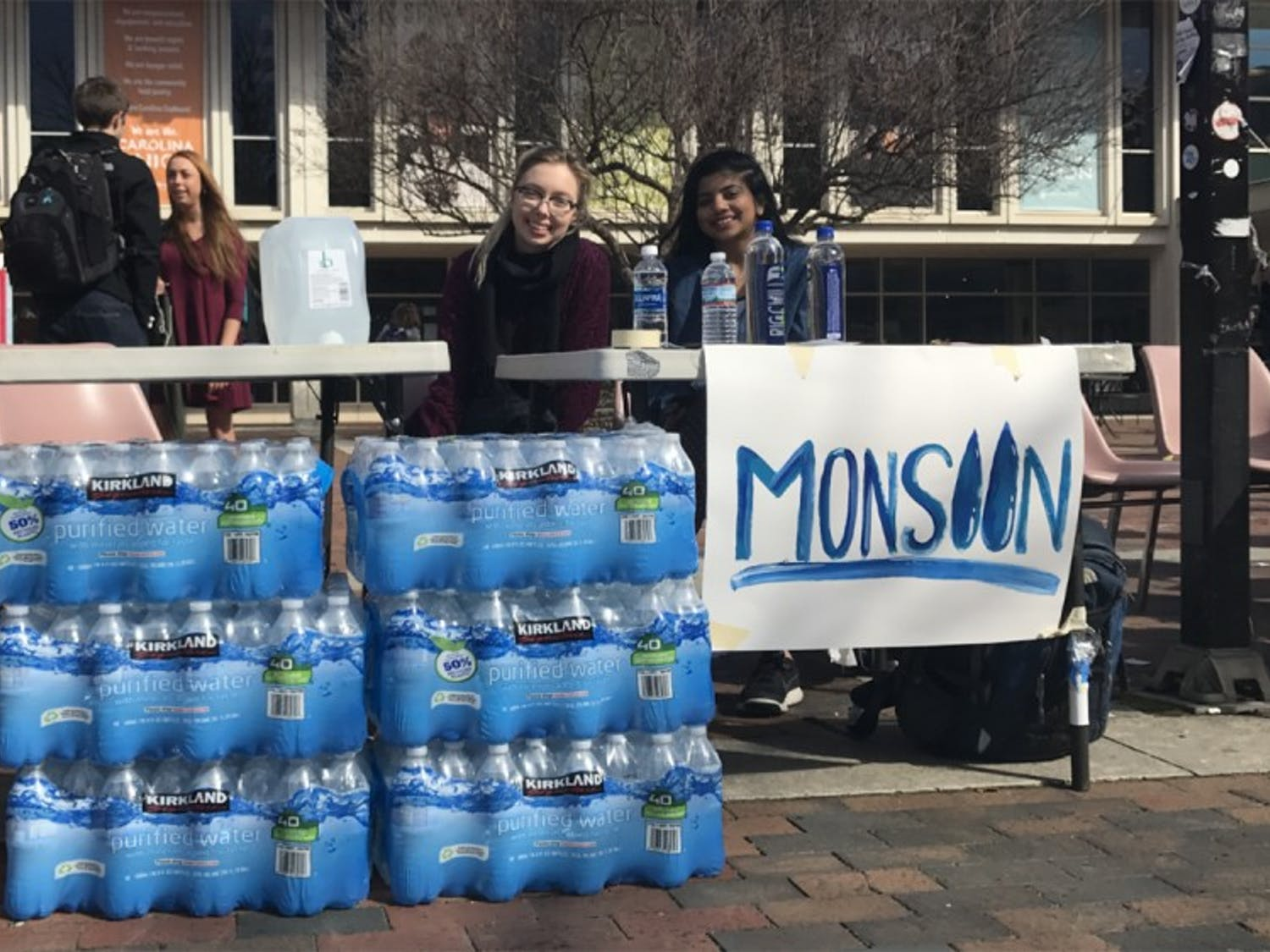 (From left) Juniors Allory Vors and Shilpa Kancharla collect water bottles on behalf of Monsoon to be sent to Flint, Mich., for relief.