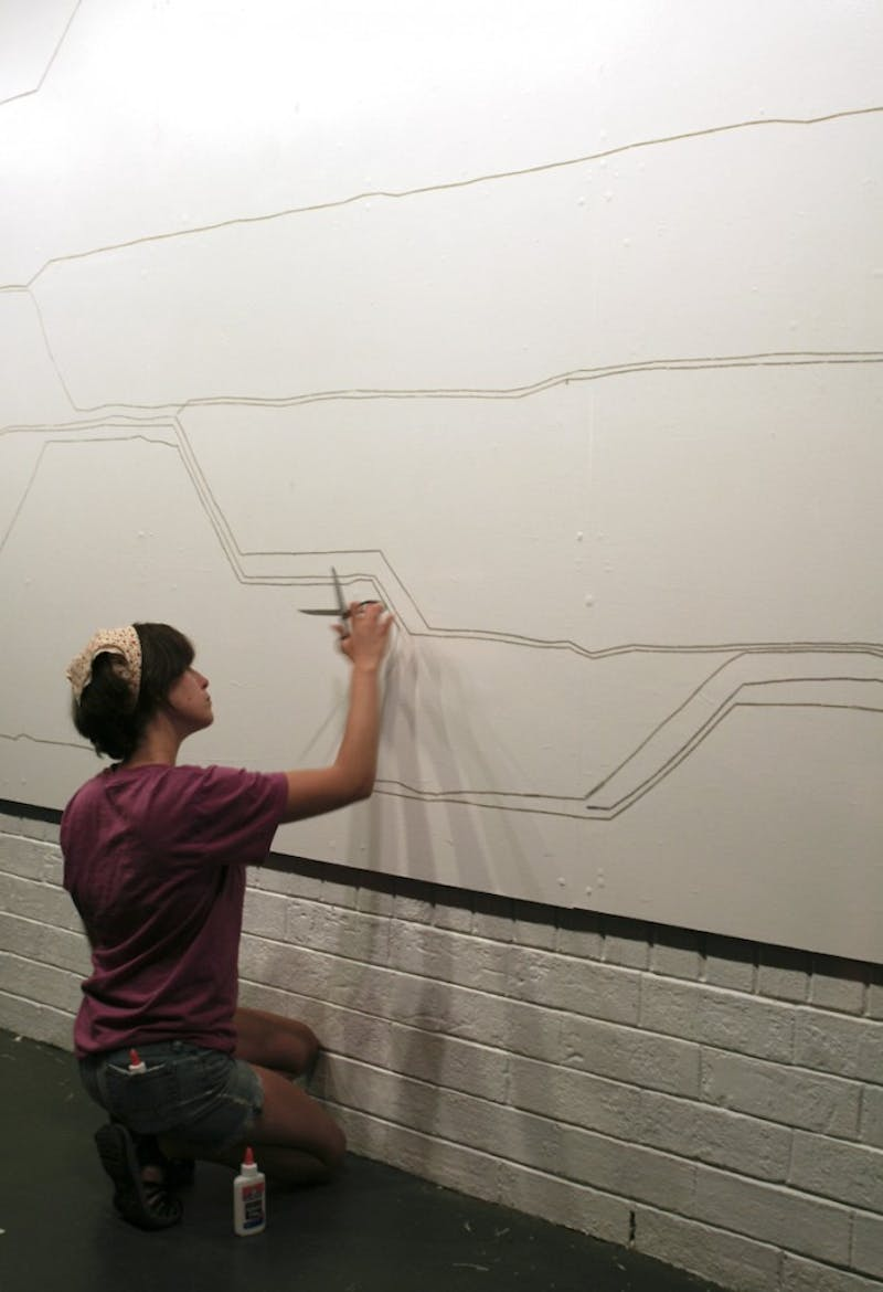 "Hannah Lamar Simmons works on on her piece ""The Paths I Trace Are The Stories You Tell"" in The ArtsCenter."