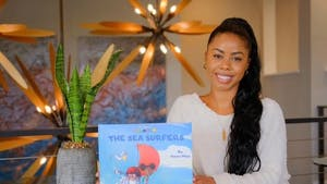Sakari Milan, UNC alumna and author, with her book The Tales of Camelia B.: The Sea Surfers. Photo courtesy of Milan.