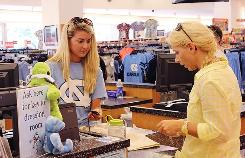 Morgan Sims,  a senior Exercise and Sports Science major, helped UNC nurse Kim Bossian check out at UNC Student Stores.