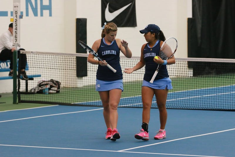 Juniors Kate Vialle and Ashley Dai celebrate during their doubles match on Wednesday against Duke. The pair lost during doubles.
