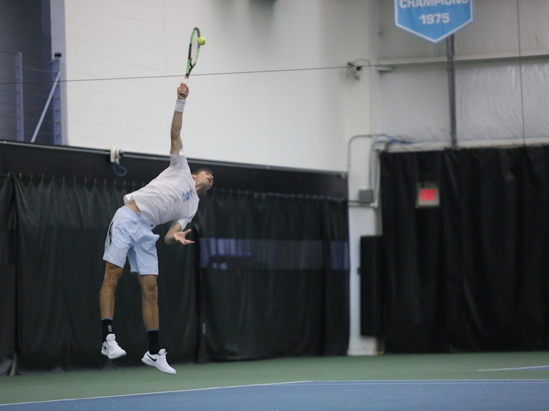 UNC men's tennis sophomore Benjamin Sigouin serves the ball to Boston College's Derek Austin during a singles match on Friday April 5, 2019. UNC defeated Boston College 5-1.