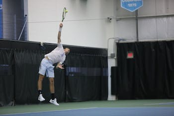 UNC men's tennis sophomore Benjamin Sigouin serves the ball to Boston College's Derek Austin during a singles match on Friday April 5, 2019. UNC defeated Boston College 5-1.