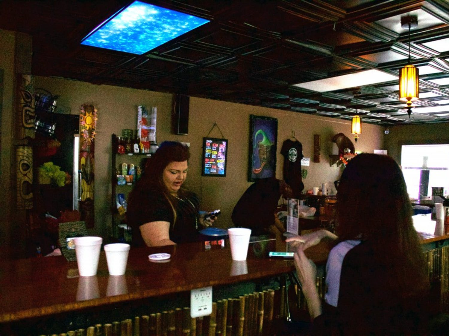Elizabeth Gardner, owner of Krave in Carrboro, serves a customer the bar's signature Krush drink. Krush is made with kava and kratom plants, creating an earthy taste with relaxing effects.
