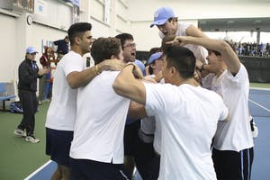The UNC men's tennis team mobs senior Brett Clark after he won his match in three sets to secure the team's victory over No.5 Oklahoma 4-3.