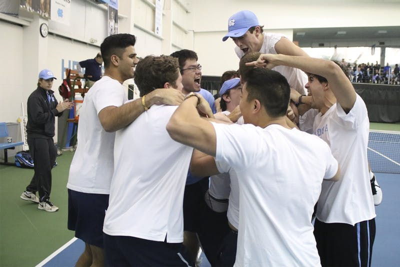 No. 7 UNC Men's Tennis team mobs senior Brett Clark after he won his match in three sets to secure the team's victory over No.5 Oklahoma 4-3 Sunday afternoon.