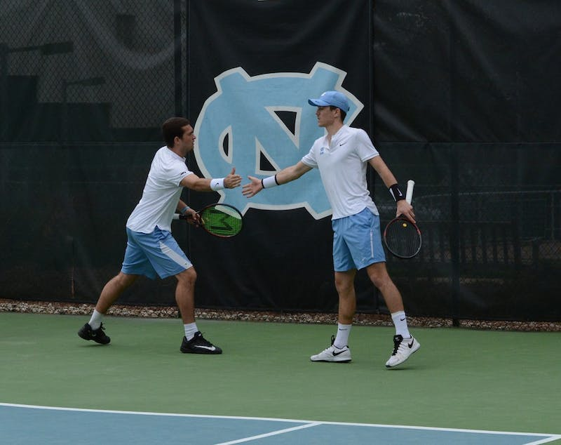 Will Blumberg (left) high fives doubles partner Robert Kelly (right) in Saturday's doubles match against Tulsa.