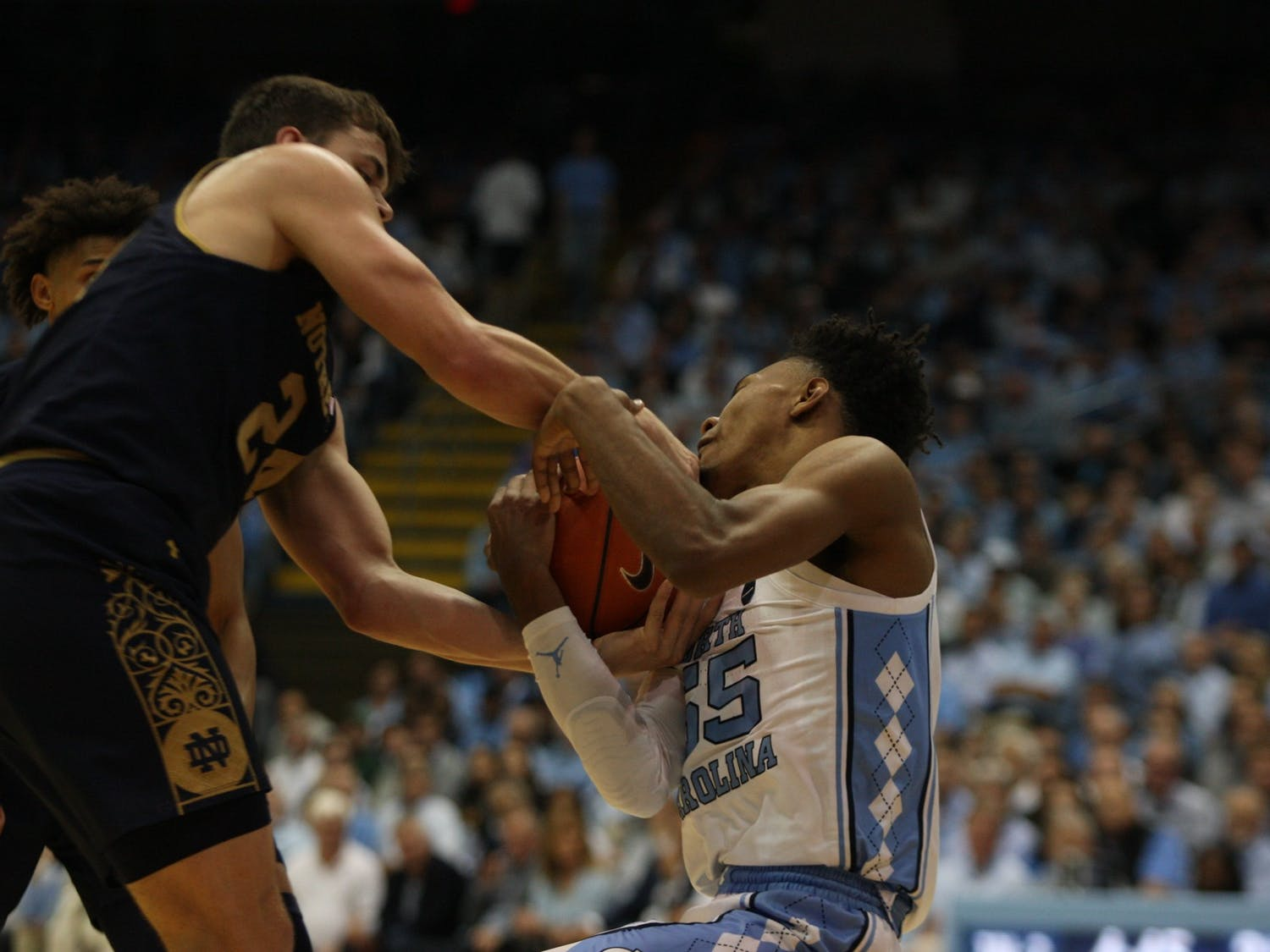 UNC guard Christian Keeling (55) and Notre Dame guard Robby Carmody (24) attempt to rip the ball out of each other's hands on Wednesday, Nov. 6, 2019 in the Dean E. Smith Center. The Tar Heels beat the Fighting Irish 76-65.
