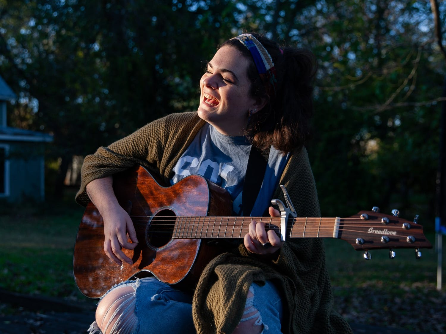 Junior communications major Lizzy Campbell sings and plays her guitar in front of her home on Monday, Nov. 16, 2020. Campbell is one of many UNC musicians who turned to online platforms to perform in 2020.