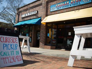 A sign advertising curbside pickup stands outside the Trolly Stop on Friday, March 20, 2020. All restaurants were forced to stop dining in services and are open only for pick up or deliveries to stop the spread of COVID-19.