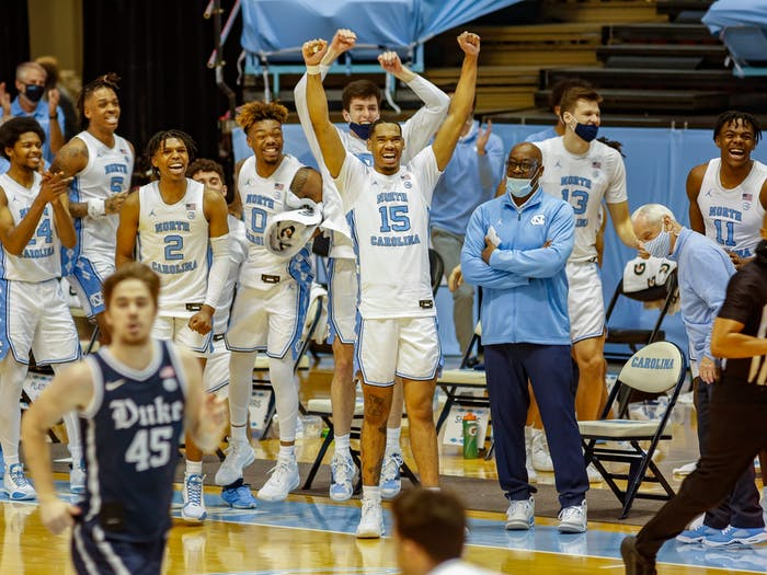 The UNC bench celebrates near the end of the game in the Dean Dome on March 6, 2021. The Tar Heels beat the Blue Devils 91-73.