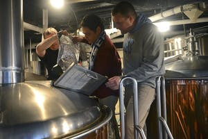From left: Rick Tufts helps Chapel Hill Mayor Mark Kleinschmidt pour hops into a vat at Triangle Brewing Company as Aaron Caracci supervises.