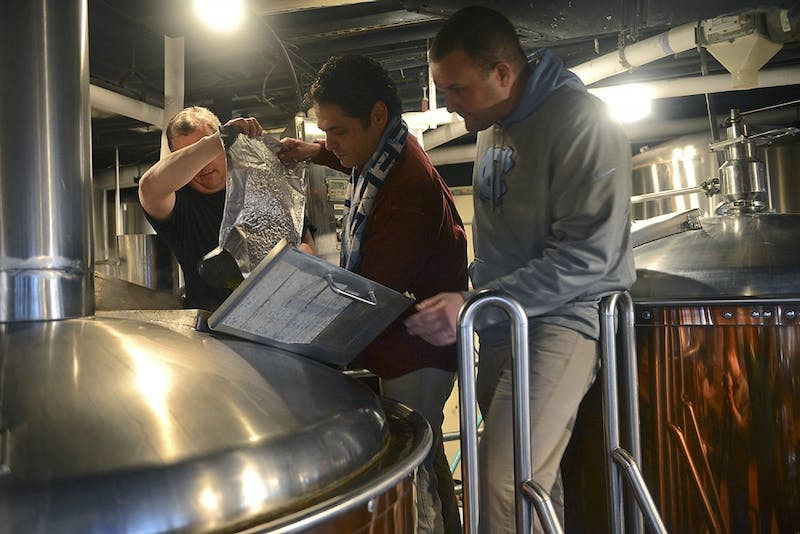 Chapel Hill mayor Mark Kleinschmidt pours hops into the Triangle Brewing Company's special game day brew for the first annual competition between the Top of the Hill and the Triangle Brewing Company Co-owner Rick Tufts (left) and co-brewmaster Aaron Caracci (right) supervise the process.