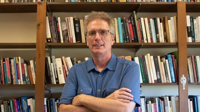 """History professor Jay Smith, co-author of """"Cheated,"""" poses in front of his collection of books on Monday, Oct. 29, 2019. Smith recently spoke with C-SPAN and the interview will air in January 2020."""
