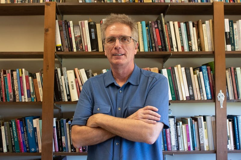 "History professor Jay Smith, co-author of ""Cheated,"" poses in front of his collection of books on Monday, Oct. 29, 2019. Smith recently spoke with C-SPAN and the interview will air in January 2020."