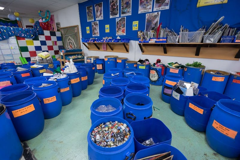 Buckets filled with items ranging from photos to stickers to old medicine bottles fill these buckets at the entry of The Scrap Exchange in Durham.