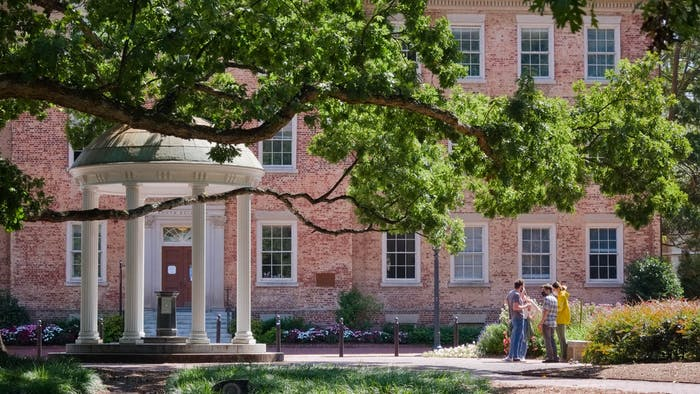 A small group stands near the Old Well behind South Building on Sept. 12, 2020.