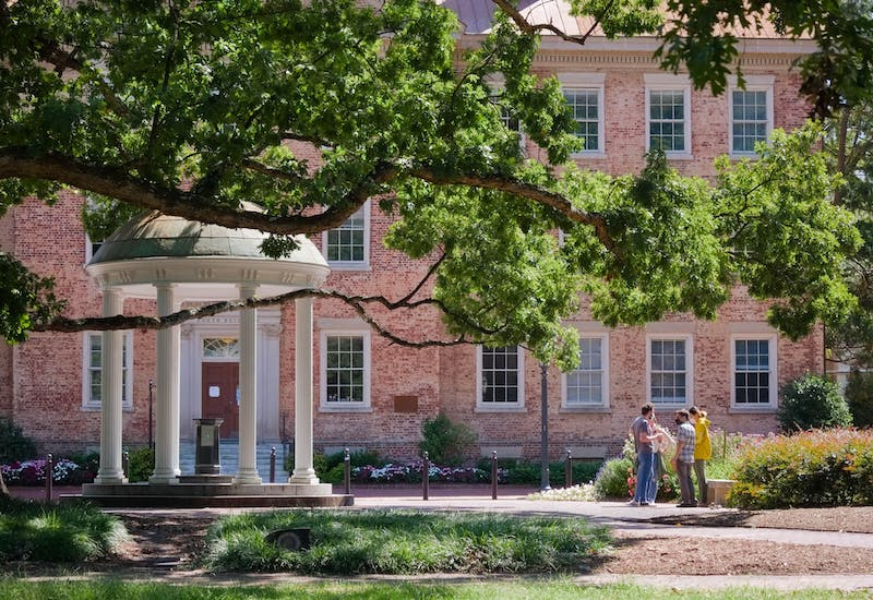 A small group stands near the Old Well behind South Building on Sunday, Sept. 12, 2020.