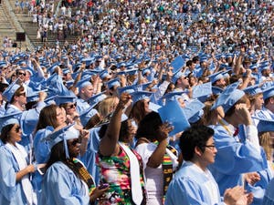 """Students raise their fists at the end of """"Hark the Sound"""" during Commencement on May 13."""