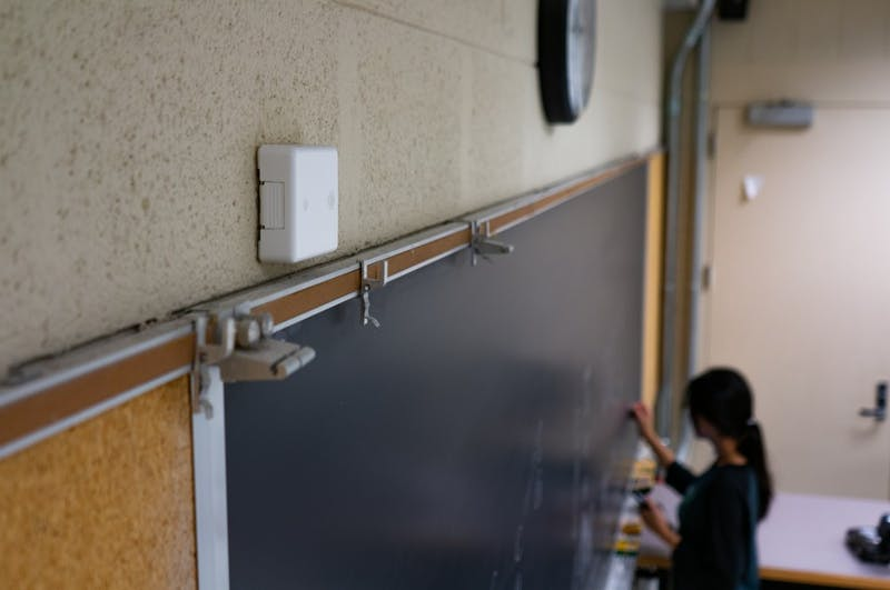 A SpotterEDU device sits at the front of the room in Hanes 117 as a student writes on the blackboard underneath on Tuesday, Oct. 16, 2019.