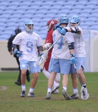 Players celebrate after midfielder Henry Schertzinger (44) scored during the game against Harvard in Kenan Stadium on Saturday, Feb. 16, 2019. UNC won 16-11.