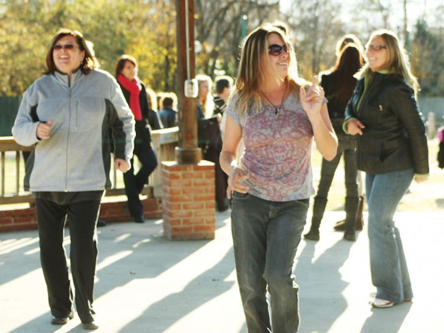 Jane Tuohey (left), Kelly Brown (middle), and Anita Akstin (right) dance in the gazebo at Town Commons in Carrboro as they wait to be in the group photo for Lovetown, USA.