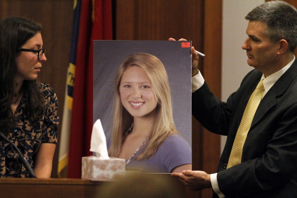 Prosecution witness Anna Lassiter, left, close friend of Eve Carson and one of her roommates is shown a large photograph of UNC student body president Eve Carson, center, by Orange Co. DA James Woodall, Jr., right,  Wednesday, Dec. 7, 2011 during the first day's testimony in the murder trial of Laurence Alvin Lovette.