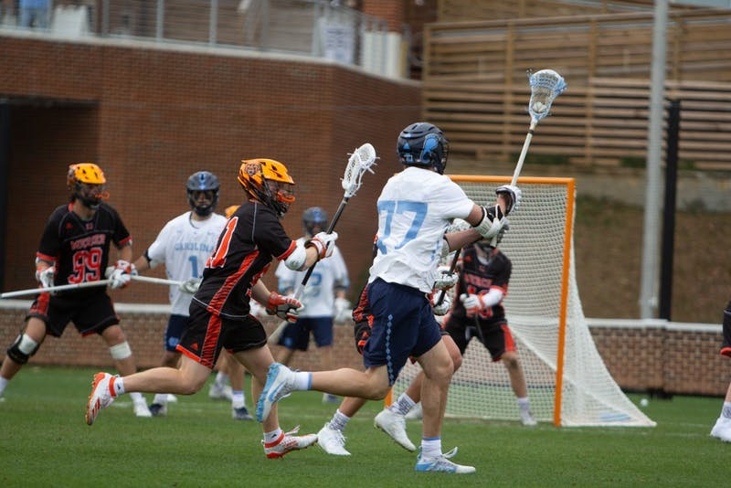 Senior midfielder Tanner Cook (77) holds the ball against Mercer at Dorrance Field on Saturday, Feb. 8, 2020. The Tar Heels beat the Bears 14-6.