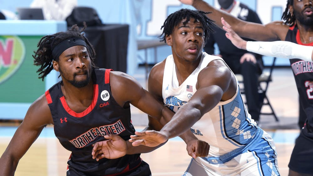 UNC first year Day'Ron Sharpe (11) blocks a Northeastern player during a game in the Smith Center on Wednesday, February 17, 2021. Photo courtesy of Jeff Camarati.