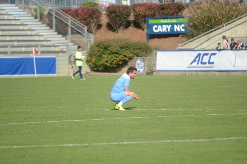 UNC senior defender Alex Comsia (4) squats on the field after the 0-1 loss against Louisville for the ACC Championship at WakeMed Soccer Park Sunday, Nov. 11, 2018.