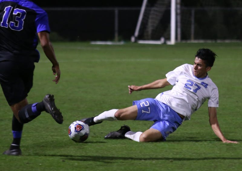 Sophomore defender Mark Salas (27) slide tackles the ball out of Duke's Ian Murphy's control. UNC men's soccer beat Duke 2-1 during the semi-finals of the ACC Championship.