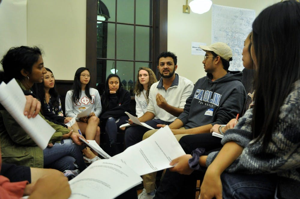 <p>Students participate in a reflection activity during an open forum hosted by the Asian American Center Student Advisory Board at Campus Y's Anne Queen Lounge on Thursday, Oct. 24, 2019. The forum gave attendees the chance to learn about the movement to establish an Asian American Center on campus.</p>