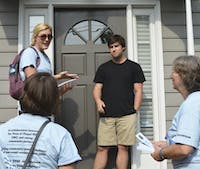 Spencer Goodson, Megan Wooley-Ousdahl, and Kay Pearlstein stand outside Turner Alvernaz's home as part of the Good Neighbor Initiative.