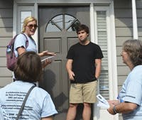 Spencer Goodson, Megan Wooley-Ousdahl, and Kay Pearlstein stand outside Turner Alvernaz's home as part of the Good NeighborInitiative.