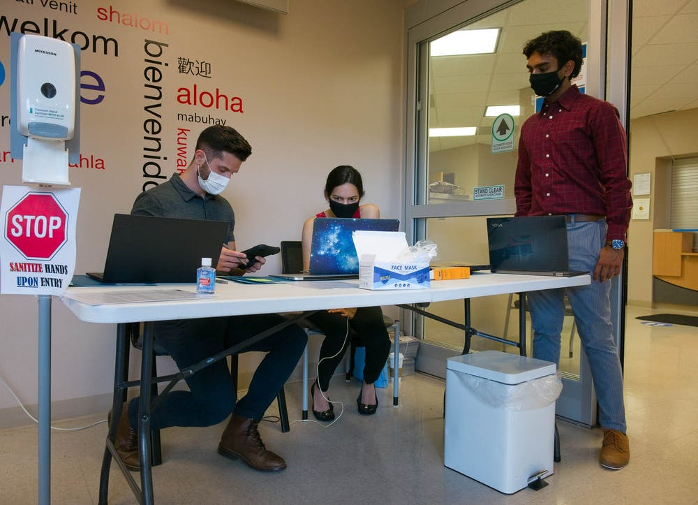 Kevin Welch (first-year medical student),  Darshana Panda (first-year medical student), and Ainesh Jain (Business Administration/Pre-Med '23) work at the check-in desk for the SHAC Medical Clinic on Wednesday, May 5, 2021.