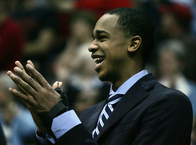 Junior John Henson cheers on from the bench where he spent the entire game due to a wrist injury from the game against Maryland.