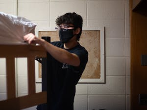 Isaac Williamson, a first year biomedical engineering major, puts sheet on his bed at Ehringhaus Residence Hall on Friday, Jan. 15, 2021.