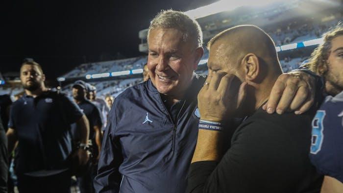 Head Coach Mack Brown and Offensive coordinator Phil Longo celebrate UNC's win on Saturday, Oct. 26, 2019. UNC defeated Duke 20-17.
