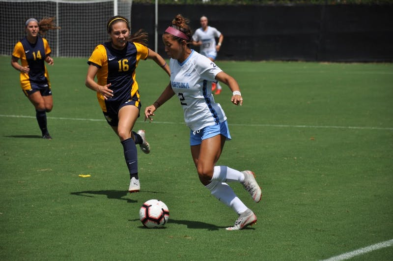 Forward (2) Sydney Spruill dribbles past defender (16) Katie Koker during Sunday's game against Marquette.