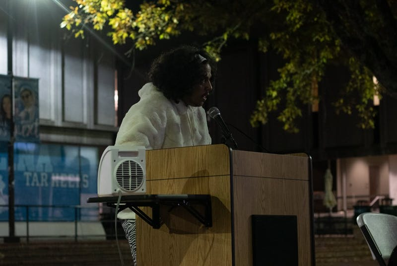 Poet Amir Rabiyah reads poems honoring trans people who have lost their lives in the past year. UNC LGBTQ Center held a candlelight vigil remembering the lives of trans people who died in the past year as part of Transgender Day of Remembrance in the Pit on Wednesday, Nov. 20, 2019. in the Pit on Wednesday, Nov. 20, 2019. the Pit on Wednesday, Nov. 20, 2019.