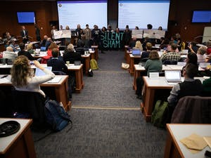 """Activists make demands for Interim Chancellor Kevin Guskiewicz on the floor of the Faculty Governance Council for """"Reparations, retract or resign"""" on Friday, Dec. 6, 2019 in Kerr Hall. They referred to a settlement between the University and the Sons of Confederate Veterans to give the SCV Silent Sam and a trust fund of $2.5 million."""