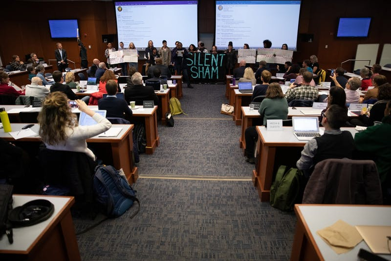"Activists make demands for Interim Chancellor Kevin Guskiewicz on the floor of the Faculty Governance Council for ""Reparations, retract or resign"" on Friday, Dec. 6, 2019 in Kerr Hall. They referred to a settlement between the University and the Sons of Confederate Veterans to give the SCV Silent Sam and a trust fund of $2.5 million."