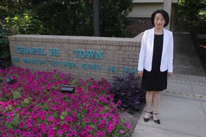 Chapel Hill town council candidate Hongbin Gu poses for a portrait in front of the Chapel Hill Town Hall building.
