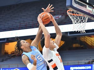 Mar 1, 2021; Syracuse, New York, USA; Syracuse Orange center Jesse Edwards (14) struggles to take a shot as North Carolina Tar Heels forward Armando Bacot (5) applies pressure in the first half at the Carrier Dome. Photo courtesy of Mark Konezny/USA TODAY Sports
