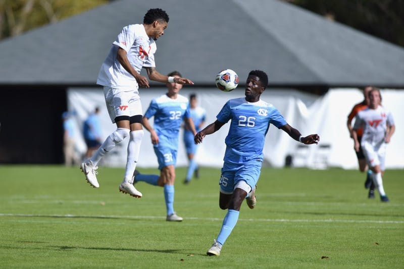 Junior forward Jelani Pieters (26) dodges a ball from a Virginia Tech header.  UNC defeated Virginia Tech 3-0 at Finley Field on Sunday Nov. 4.