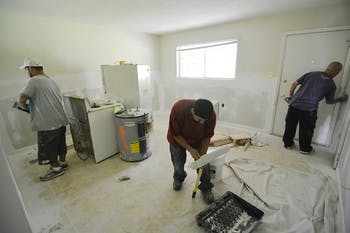 Brothers, Jay Lopez (left), Oscar Lopez, and Luis Lopez work on renovating the condemned apartments at Camelot Village.